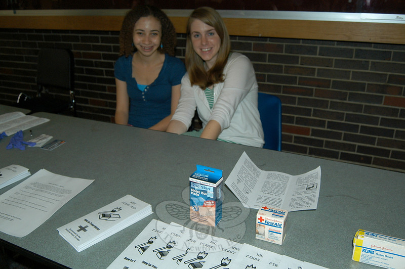 Newtown High School National Honor Society students Erica Green, left, and Sarah Walton waited at a booth in the school's lobby on Wednesday, June 7, to share information with passing students on first aid. Sarah was a co-organizer for the event with Matthew Jensen.  (Hallabeck photo)