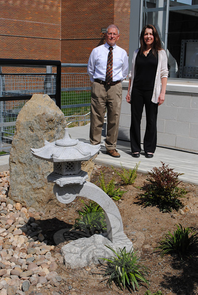 Regina DelRossi stands with horticulture instructor Robert Herman, who oversaw her de-sign and installation of a garden to honor the late Professor Eugene Wisniewski.  (Crevier photo)
