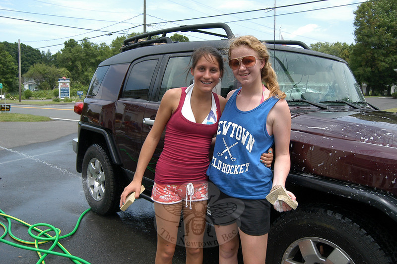 Newtown Ecumenical Workcamp students Lexi Black (left) and Jessica Haitz worked during a car wash with fellow NEWS workcampers on Saturday, June 5, held in the parking lot of Century 21-The Scalzo Group at 48 Main Street South. The group was raising funds for their July 3–10 trip to Biloxi, Miss., where they will provide home repairs for Gulf Coast residents who are still recovering from Hurricane Katrina. The students worked to clean cars and trucks at the event in exchange for donations of any amount.  (Hallabeck photo)