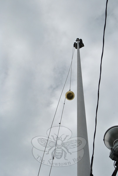 The regilded ball that tops Main Street's flagpole makes its way up a pulley system on June 9, where Valley Restoration owner Paul Bastiaanse awaits its arrival.  (Crevier photo)