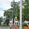 On Wednesday morning, June 9, Moe Bastiaanse, left, and Robert Bastiaanse of Valley Restoration in Torrington used a pulley to bring the newly repainted flagpole finial to the top.  (Crevier photo)