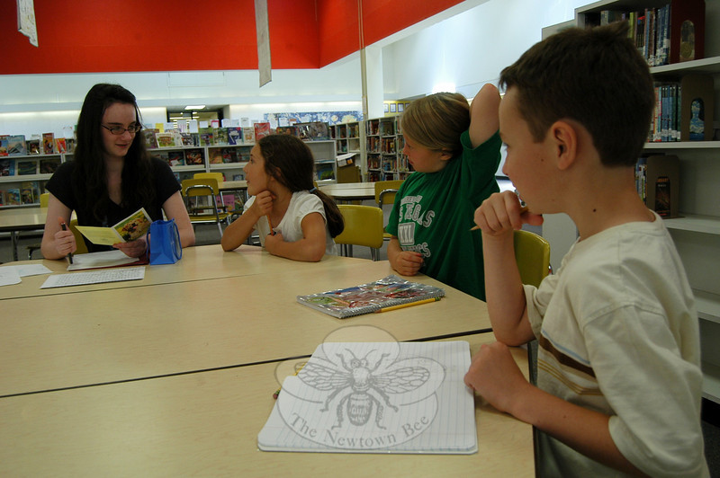 Newtown High School freshman Lillia McEnaney, left, and Head O' Meadow third graders, from left, Kendra Saunders, Katie Sailer, and Michael Arena worked on a story written by the students with Lillia's guidance on Monday, June 7, the last meeting of the school year for the group.  (Hallabeck photo)