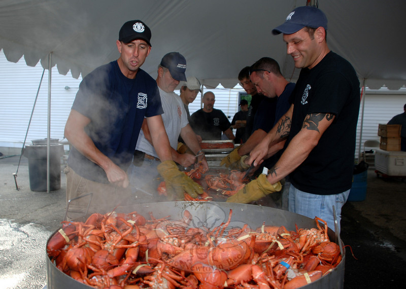 By the hundreds, lobsters fell from the steaming pot and hit the aluminum surface where Sandy Hook Firefighters Jeff Thomas, left, and Quinn Fontaine were first to slide them down the line.