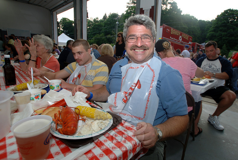 Rich Stein was bibbed and ready for his 14th Lobsterfest. All around him are residents talking, laughing, and cracking tails for the tender meat.  (Bobowick photo)