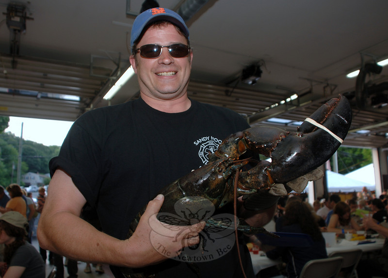 Deputy Director of Land Use and Sandy Hook Volunteer Fire & Rescue Firefighter Rob Sibley shed his municipal and volunteer hats for a casual cap during the June 11-12 Lobsterfest at the fire station on Riverside Road. With him is one of the 10-plus-pound lobsters that were raffled during the course of the two-night event.   (Bobowick photo)