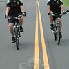 Police Officer Jason Flynn, left, and Officer Leonard Penna ride their police bicycles on a roadway at Fairfield Hills earlier this week. The two men, who are school resource officers at Newtown High School and Newtown Middle School, respectively, do police patrol work on bicycles in the summertime.   (Gorosko photo)