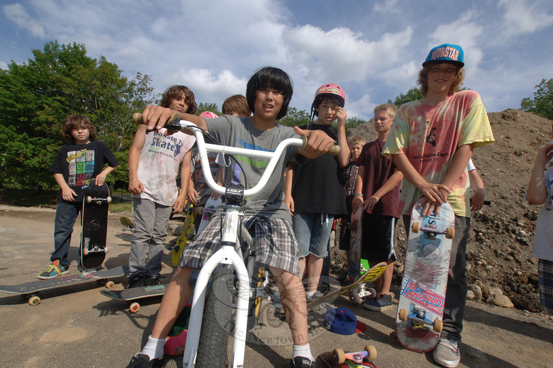 Propped on his BMX bike, Julian Lewis gathers with skateboarders and other bike riders at Dickinson Park where a new skate park is being installed this summer. Site work has al-ready begun.  (Bobowick photo)