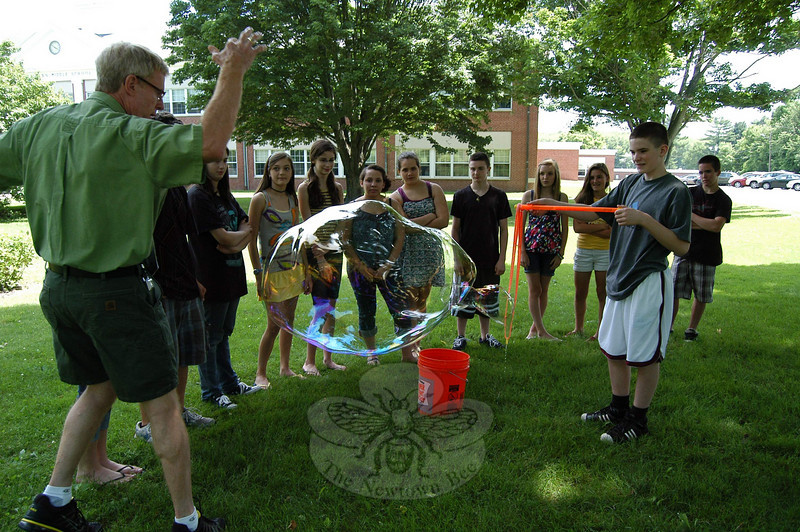 Newtown Middle School Technology Education teacher Don Ramsey, left, demonstrated the chemistry behind making bubbles for students on Tuesday, June 15, on the front lawn of the school.  (Hallabeck photo)