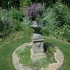 A pedestal holding an urn full of vertical purple blooms serves as the visual centerpiece of Mrs Sander's garden.  (Gorosko photo)
