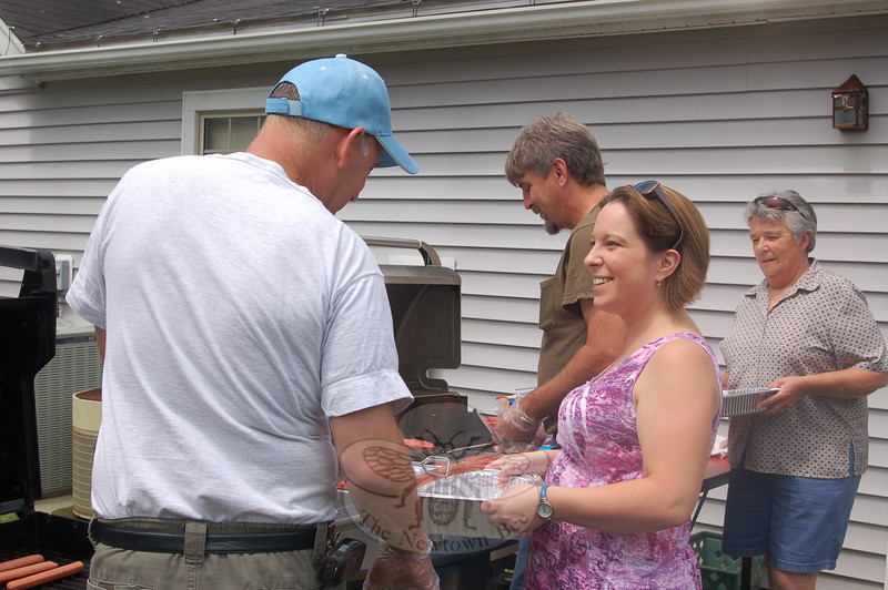 Rudy Anzellotti, left, and Dennie Dyess staffed the grills behind the Nunnawauk Meadows Community Room on Thursday, June 24, while kitchen site manager Zandra Thompson and volunteer Marie McLenithan stand ready to move the cooked hot dogs and hamburgers into the dining room. Residents of Nunnawauk Meadows enjoyed tortellini and potato salads, coleslaw, and baked beans made by Ms McLenithan, as well, at the Annual Nunnawauk Meadows Residents' Association Picnic. The luncheon was preceded by a rousing game of Bingo, and the celebration finished up with watermelon and cake for dessert.  (Crevier photo)