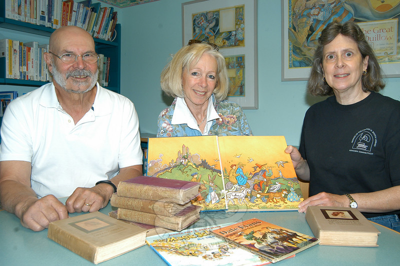 From left, rare books expert John Renjilian, Janice Bernard, and Denise Kaiser show off the rich artwork of a children's classic collectible. Shoppers at the annual book sale often find beautiful artwork an appealing feature of a collectible. A stack of rare Horatio Alger, Jr, books is stacked in front, along with an inscribed Magic School Bus book, a first edition Golden Book, and two L.M. Montgomery books that will be sold at the July Friends of the C.H. Booth Library Book Sale.  (Crevier photo)