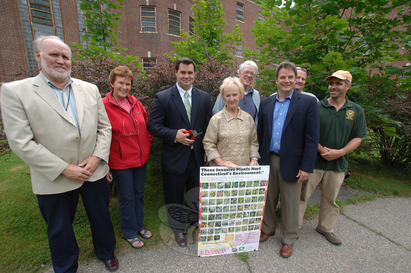 Land Use Director George Benson, left, stands with Martha Wright, State Representative Chris Lyddy, who holds garden pruners, First Selectman Pat Llodra, who displays an invasive species identification board, Conservation Commission Chair Joe Hovious over her shoulder, and beside her is Land Use Deputy Director Rob Sibley. On the far right is Parks and Recreation Department member John Moore. Assistant Director of Parks Carl Samuelson is beside Mr Moore.  (Bobowick photo)