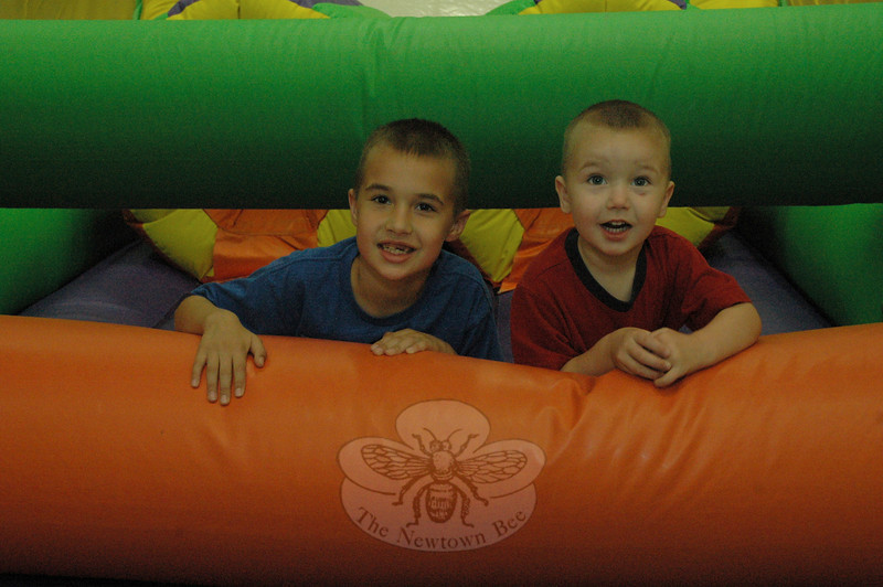 The Hanson brothers, Max, 8, left, and Charlie, 3, had some fun on an inflatable playground toy that was set up inside one of the large field houses at Newtown Youth Academy. The inflatable toy provided recreation for children at the Light the Night kickoff event.  (Gorosko photo)