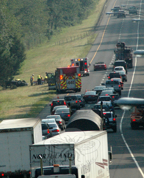 A traffic backup formed on eastbound Interstate 84 on Wednesday, July 7, following a one-car rollover accident that ended on the highway median. State police said that motorist Rosemary Loconte, 26, of Carmel, N.Y., was driving a 1999 Pontiac Sunfire coupe in the left lane of two lanes on eastbound I-84 at about 8:21 am about 2,000 feet east of the Philo Curtis Road overpass, when the auto went off the left side of the road, struck a highway reflector post on the median, returned to the road and then went back onto the median where it struck a tree and then rolled over, landing on its roof. Loconte was able to unbuckle her seatbelt and crawl out of the overturned car, state police said. An off-duty Danbury firefighter, who was driving behind Loconte at the time of the accident, went to her aid, said Sandy Hook Fire Chief Bill Halstead. Sandy Hook firefighters went to the accident, in which the auto was destroyed. Loconte, who was conscious and alert, received no serious injuries, according to officials. Newtown Ambulance volunteers transported her to Danbury Hospital.  (Gorosko photo)