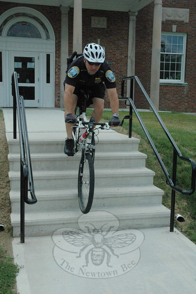 Police Officer Leonard Penna demonstrates how to ride a bicycle down a stairway in the event that such a maneuver is needed during the course of police patrol work on a bicycle. Officer Penna and Officer Jason Flynn have started their summertime patrols of town on police mountain bikes.  (Gorosko photo)