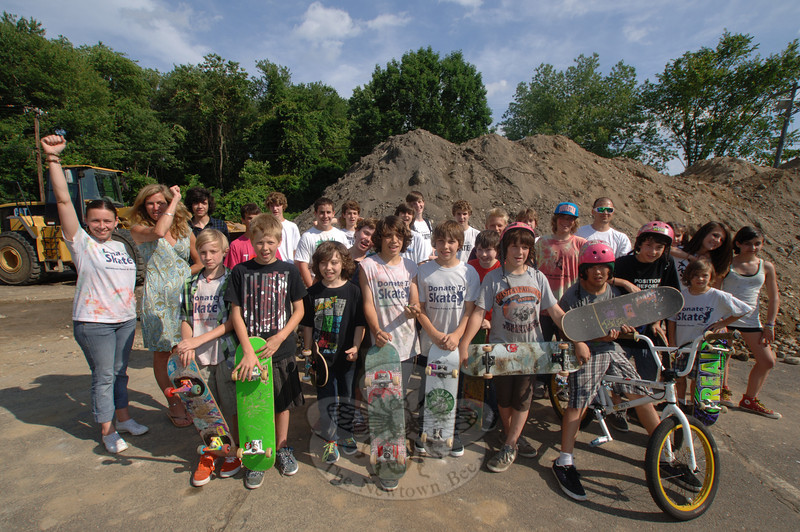Skaters, BMX riders, Donate to Skate Campaign Chairman Erin Heneghan and Parks and Recreation Director Amy Mangold, at left waving and cheering, gathered June 23 in the late afternoon to see the start of work for the new skate park at Dickinson Park.  (Bobowick photo)