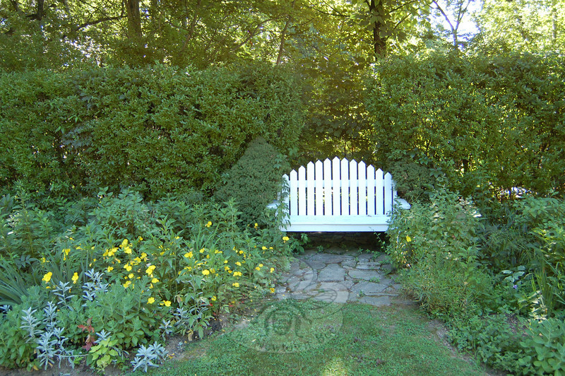 The wooden bench built by Bob DeCosta is the focal point of a shade garden, one of several gardens Barbara DeCosta nurtures on their property. A tall privet hedge, planted when the DeCostas bought their home 24 years ago, is the backdrop for this garden.  (Crevier photo)