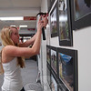 Newtown High School student Kateleen Foy hangs photography she took while working with photographer Laurie Klein in preparation for the current art exhibit at the Danbury Mayor's Office.  (Hallabeck photo)