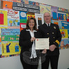 Reed Intermediate School art teacher Angela Choniski received an award from Deputy Fire Marshal Michael Zilinek on January 22 for her help in guiding the fifth grade art students there who participated in the Connecticut Fire Prevention Poster Contest. The annual statewide contest publicizes the need for fire prevention awareness. On display behind Ms Choniski and Mr Zilinek are some examples of the hundreds of fire prevention posters that the art students made. The posters are on display in the school's main lobby.  (Gorosko photo)