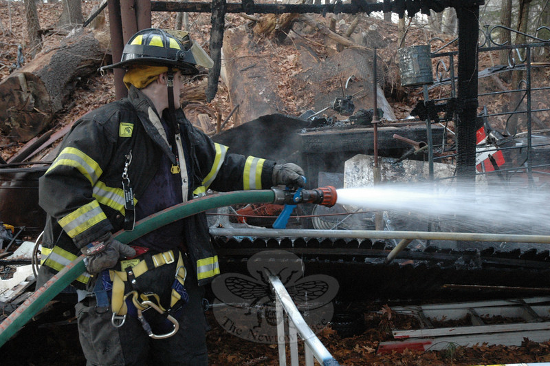 Botsford volunteer Firefighter Jason Brower sprays some water onto a smoldering assortment of junk, debris and used power equipment which had been stored at a fenced compound at a residential property at 265 South Main Street at about 4:15 pm on January 22. Another Botsford firefighter who had been driving through the area noticed that a fire was underway at the property and called firefighters to put out the blaze. There were no injuries. The cause of the fire is undetermined.  (Gorosko photo)