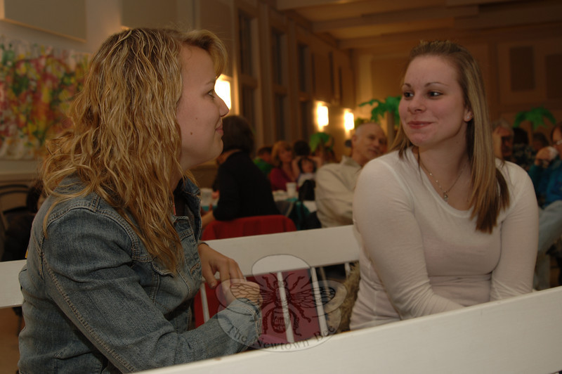 Karen Whippie, left, talks with her friend Samantha Harrison during the Haiti Dinner & Reggae Night at Newtown Congregational Church on January 23. Behind them in the church hall are guests finishing their dinner as the band gets ready to play.  (Bobowick photo)