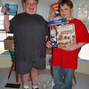 Tyler Sherwood, left, and his twin brother, Jason, stand in front of seven boxes of books, DVDs, games, and other items they have collected in just one month, to donate to Yale Children's Center. Tyler has been treated for various non-life-threatening conditions at the Children's Center, and wants to make the hospital stay easier for other children who must be there for extended periods of time. The boys will continue accepting donations at boxes set up at various locations in Newtown through the end of May.  (Crevier photo)