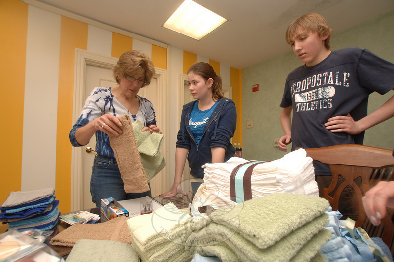 Newtown United Methodist Church members, from left, Betsy and Aspen Kraushaar, and Cameron Eiseman, helped residents of The Homesteads recently pack up items that had been collected for the residents of Haiti.  (Bobowick photo)