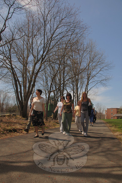 At a brisk pace, in front and from left, are town personnel from various departments, Kim Cadena, Sue Marcinek, and Amy Mangold. The group walked the trails at Fairfield Hills from a starting point at the new Newtown Municipal Center.  (Bobowick photo)