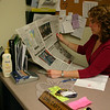 Sandy Hook Volunteer Fire & Rescue Co. Secretary Karin Halstead reads a story in the Canadian newspaper The Intelligencer, which talked about the gear that was recently returned to her fire company. The widow of a Canadian volunteer firefighter donated the items to her local fire department, who in turn decided to find where the gear had originated.  (Hicks photo)