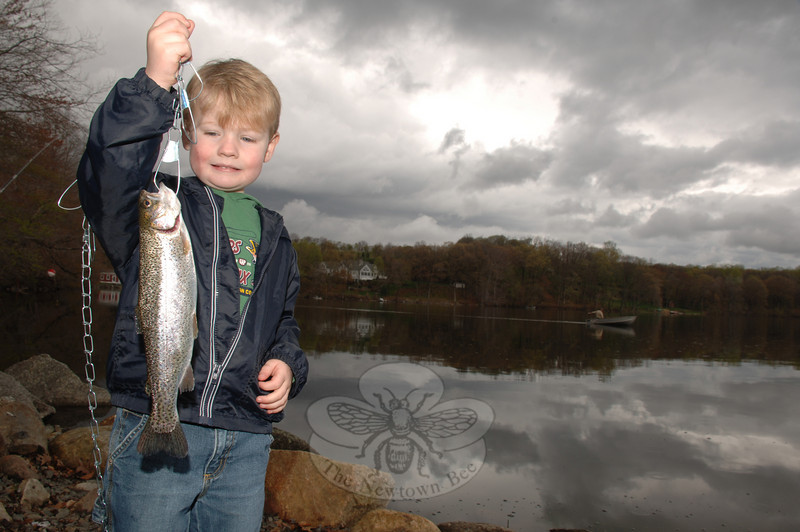 Four-year-old Eric Unger admires his first catch, a beautiful trout, with a mix of pride and trepidation at Taunton Lake on opening day.  (Bobowick photo)