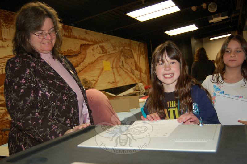 Democratic Registrar of Voters LeReine Frampton oversaw Head O' Meadow student Grace Pettinelli on Monday, April 26, using a voting machine for the first time to cast her vote on the categories of books she would like to see purchased for the school's library.  (Hallabeck photo)