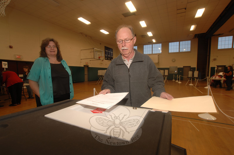 Former Finance Director Benjamin Spragg slips his ballot sheet into the machine Tuesday evening.  (Bobowick photo)