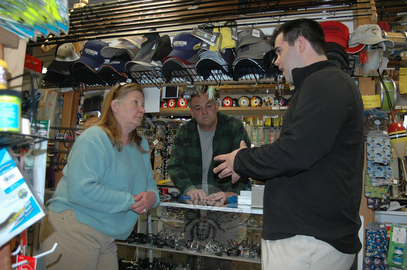 Newtown State Representative Chris Lyddy, right, chats with Newtown Bait & Tackle own-ers Rich and Jan Newman a few days after the state rolled back an unprecedented 100 per-cent increase on many sports licensing fees, including the fishing and hunting licenses the Newtown store sells as an agent for the state.  (Voket photo)