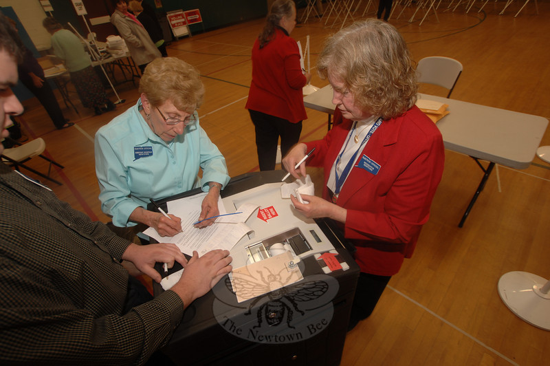 Assistant Moderator Marcia Spiegel works with Moderator Cindy Scheibel to verify the machine tally at the April 27 budget referendum.  (Bobowick photo)
