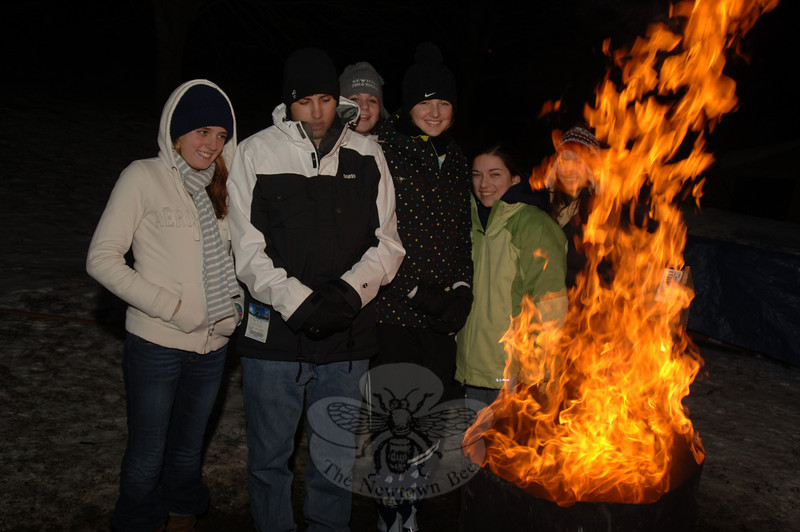 Students gathered around a campfire that was blazing during the weekend awareness-raising event at Newtown Congregational Church.  (Bobowick photo)