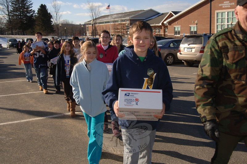 "With Valentine's Day packages stamped with ""America Supports You"" on the front, Reed Intermediate School students carried items to a mail truck on January 29. Packages were designated for the troops serving overseas.  (Bobowick photo)"