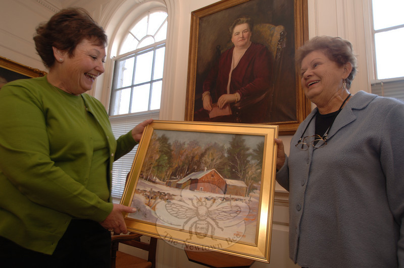 Mary Hawley Society member Marg Studley, left, helps hold artist Ruth Newquist's painting that Ms Newquist has donated for auction at an upcoming Wine and Scotch Malt Tasting fundraiser in the Alexandria Room on February 20. Above the women is a portrait of Mary Elizabeth Hawley, who gifted Edmond Town Hall to Newtown.  (Bobowick photo)