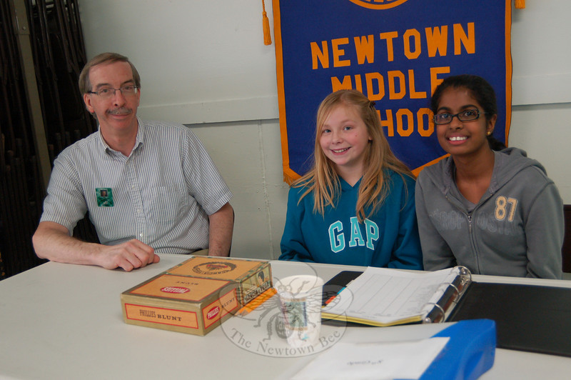Newtown Middle School's Interact Club began a fundraiser for Haiti on Monday, February 1. The club is selling wristbands for $2 each. Seen here is club advisor Bruce Moulthrop, with seventh graders Anita Luxkaramayagam, right, and Casey Demers, selling bracelets on February 1 during their lunch break.  (Halla-beck photo)