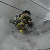 A Hook & Ladder firefighter used a chainsaw to cut a hole into the roof of a Deerfield Drive house to ventilate the home during a structure fire on Tuesday, February 2.  (Gorosko photo)