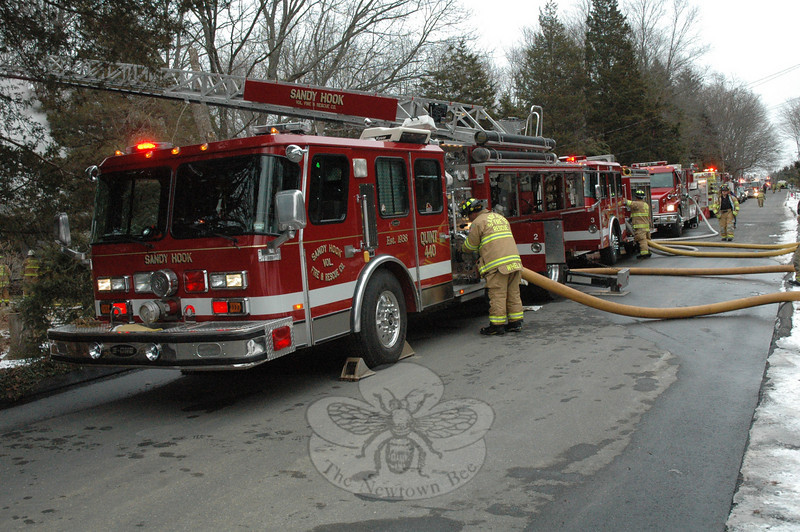 A long row of fire vehicles from six volunteer fire companies responded to the scene of a house fire on Deerfield Drive in Sandy Hook on Tuesday. Approximately 33,000 gallons of water, hauled in by tanker shuttle, was used to put out the fire (Gorosko photo)