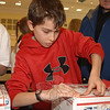 Will Huegi wrote Valentine's Day letters to troop members this year and, along with classmates, he packaged and placed postage on boxes collected by Postmaster Mark Favale at Reed Intermediate School on Friday, January 29.  (Bobowick photo)