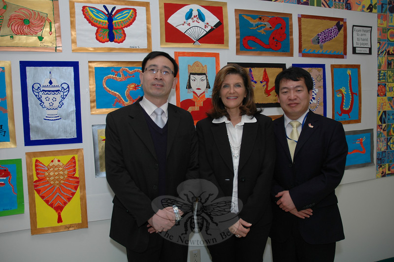 Shang Deyuan, left, is a vice principal at a primary school in China for students in grades one through six. On January 22, he was visiting Reed Intermediate School to learn how students are taught there. Also shown are Angela Choniski, center, who is an art teacher at Reed School, and Hong Ding, who teaches the Chinese language at Newtown High School. The group stood before a display of vivid posters with Chinese motifs that had been made by Reed School art students.  (Gorosko photo)