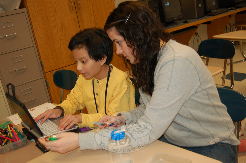 Newtown High School senior Jenn Callery, right, works with freshman Cassie Sim during a January 21 meeting of the school's Tools for Living course.  (Hallabeck photo)