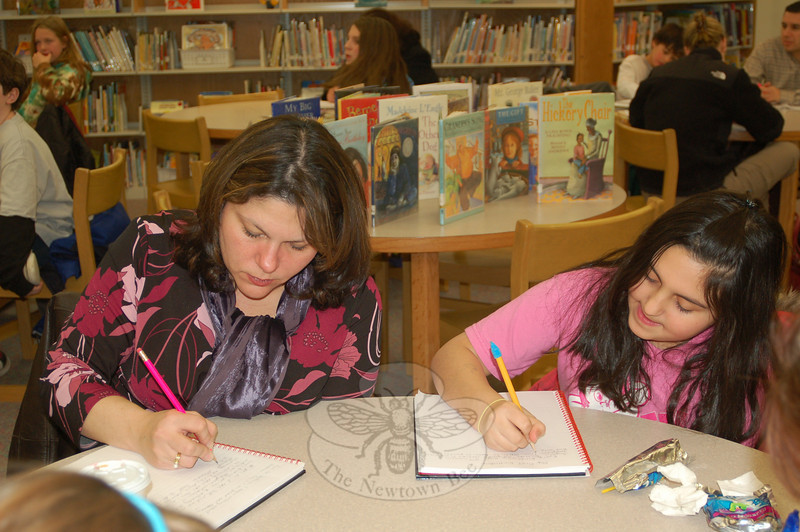 Each of the six evenings that make up the family memoir writing session include time to read, share, and of course, to write. Donna Castellano, left, and her daughter Briana focused together on writing down memories at a recent class.  (Crevier photo)