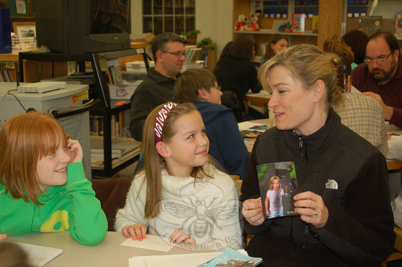 "Melissa Harkins, right, shares her memories triggered by a family photo with daughter Haley, center, and friend Hayley Lambert. The parent/child teams shared photos as a prelude to a memoir writing exercise at class, Tuesday, February 2. ""With all the activities a family has, it's good to be able to spend time with just one child doing something like this,"" said Ms Harkins.  (Crevier photo)"