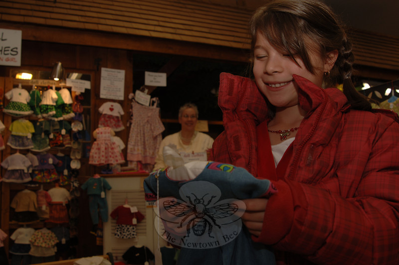 Ava Holmes looks closely at the garments she imagines would fit her dolls. Behind her is crafter Monica Weber of Roxbury.  (Bobowick photo)