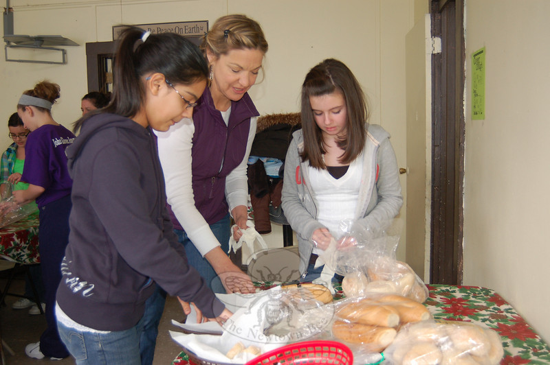 Reed Intermediate School fifth grade teacher Karen King, center, hands gloves to Girl Scouts Anika Dholakia, left, and Madison Duffy, who were working to prepare bread baskets at the Dorothy Day House on Saturday, January 30.  (Hallabeck photo)