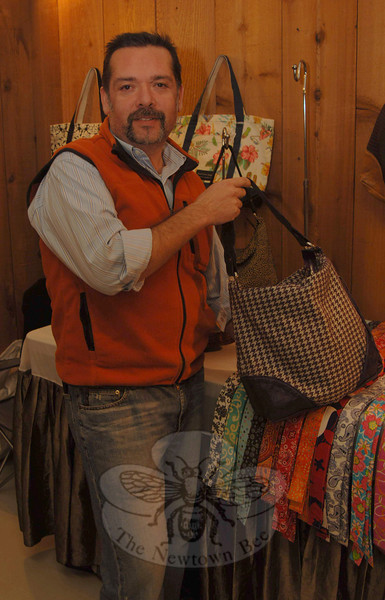 Piper Promotions of Newtown is hosting Escape the Winter Craft Show & Sale events each weekend this month at Lexington Gardens, 32 Church Hill Road. Among those at the nursery and gift shop last weekend was Marcelo Mirando, here showing one of his signature handbags.  (Bobowick photo)