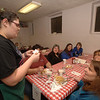 Elyse Knapp takes dinner orders for guests during this week's Shrove Tuesday at St John's Episcopal Church in Sandy Hook. At the head of her table seated across from one another are her parents Kenneth Knapp, left, and Janet Knapp, right. Beside her is Joan Giannattasio. Beside Mr Knapp are Marylin DeJoseph, and Kym Venezia and her son Christopher.  (Bobowick photo)