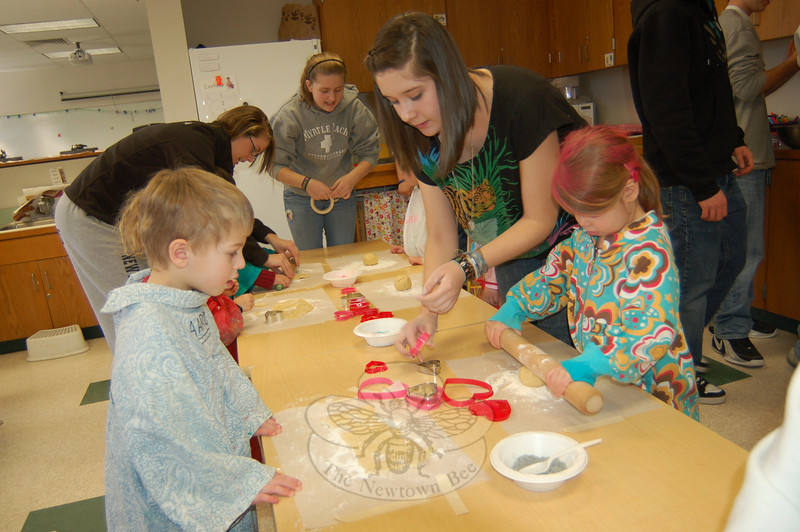 Newtown High School student Charlie Buckle, right, helped Nurtury preschoolers on Thursday, February 11, make sugar cookies as a Valentine's Day project.  (Hallabeck photo)